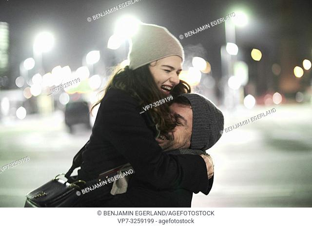couple falling in arms, embracing, laughing lovers outdoors in city at night, happiness, in Munich, Germany