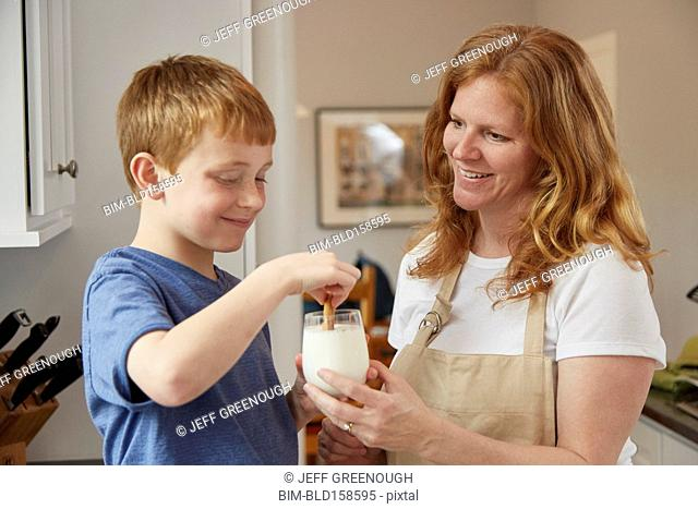 Caucasian mother and son dunking cookies in milk