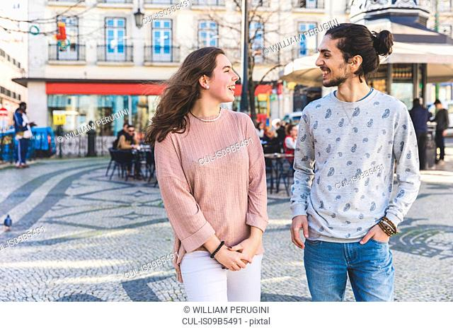 Young couple, walking outdoors, smiling, Lisbon, Portugal