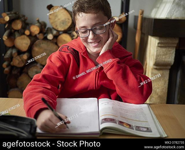 Kid doing is homework at home by the firewood, Ludiente, Castellón, Valencian Community, Spain
