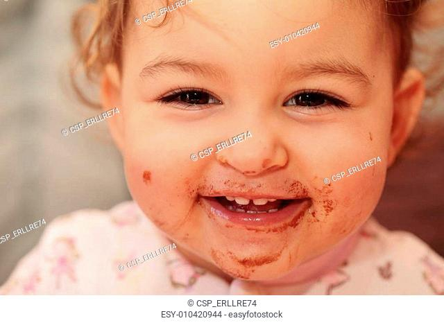 a beautiful baby smailing with a dirty mouth of chocolate