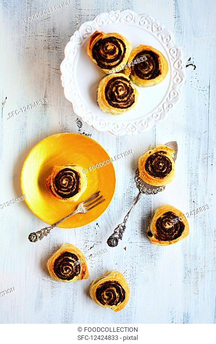 Poppy seed snails on a golden plate with a cake fork