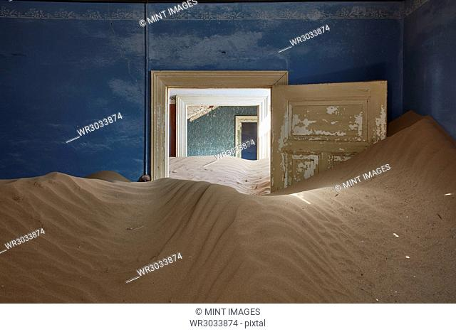 A view of a room in a derelict building full of sand