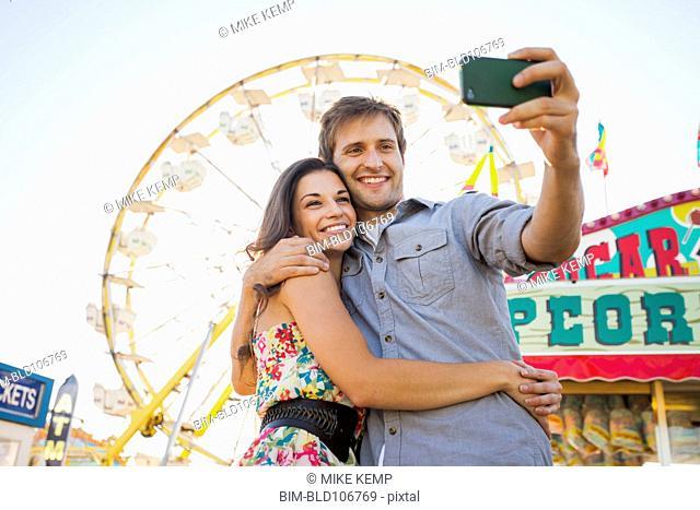 Caucasian couple taking self-portrait at carnival