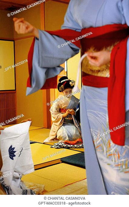 A GEIKO GEISHA DRESSING IN HER HOUSE OKIYA, THE GEIKO FIXES HER WIDE BELT OBI IN PLACE OVER HER KIMONO OBEBE WITH A FINE STRING OBIJIME, GION DISTRICT, KYOTO
