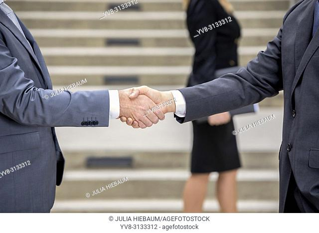 Professional handshake with female colleague in the background
