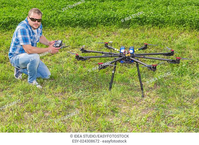 Man with remote control and multicopter on ground