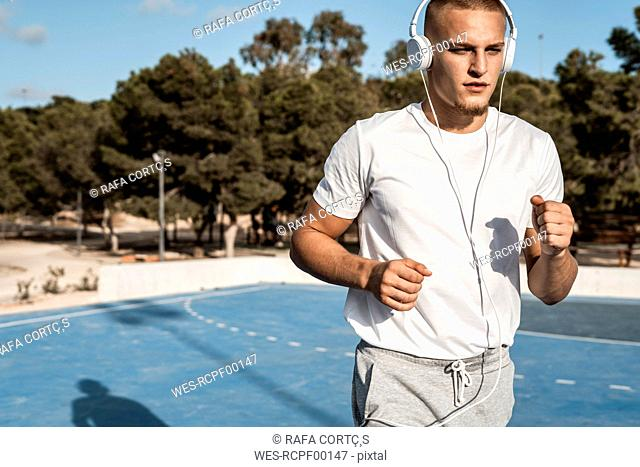 Young man with headphones running outdoors