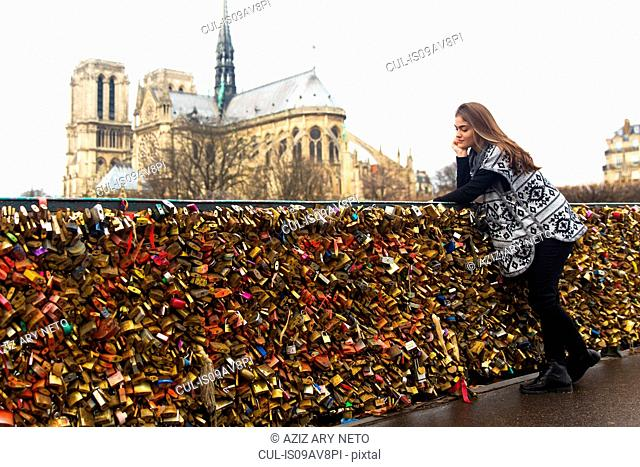 Young woman leaning against love locks, Pont de l'archeveche, Notre Dame Cathedral in background, Paris, France