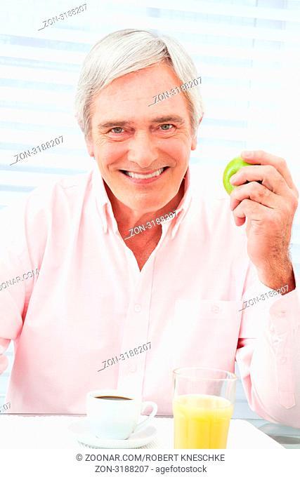 Lachender Senior sitzt mit Apfel und Kaffee am Frühstückstisch