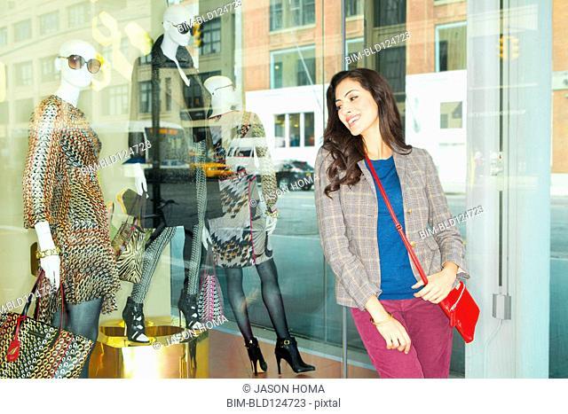 Mixed race woman window shopping in city