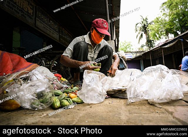 After sweeping the market the whole day a worker is collecting dry vegetables from the trash without gloves at Tehatta. The West Bengal government has...