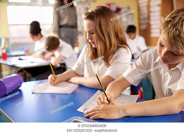 Boy and girl working in primary school class, close up