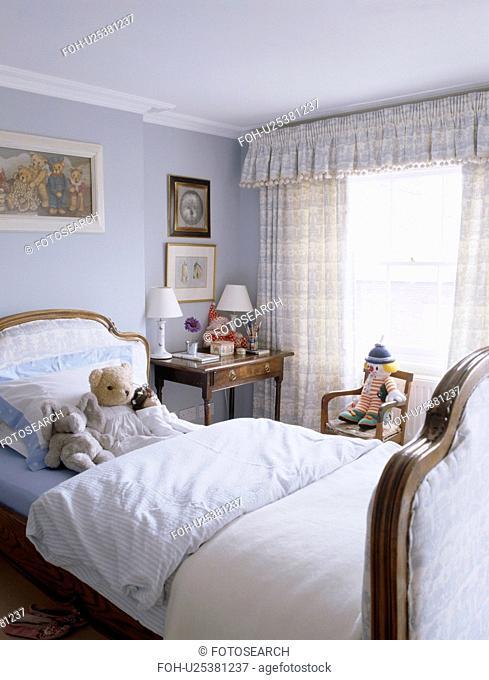 White bedlinen on upholstered bed in child's pastel blue bedroom