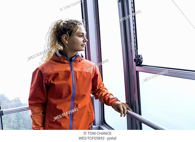 Young woman using cable car to reach the mountain