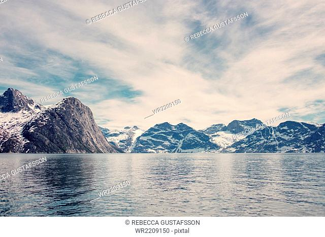 Scenic view of sea and snowcapped mountains against cloudy sky