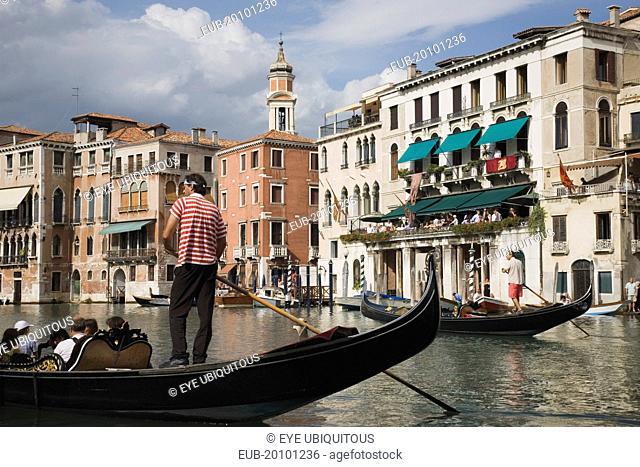 Gondolier manoeuvres gondola before start of Regata Storico the Venice annual historical Regatta in September. Canalside buildings behind
