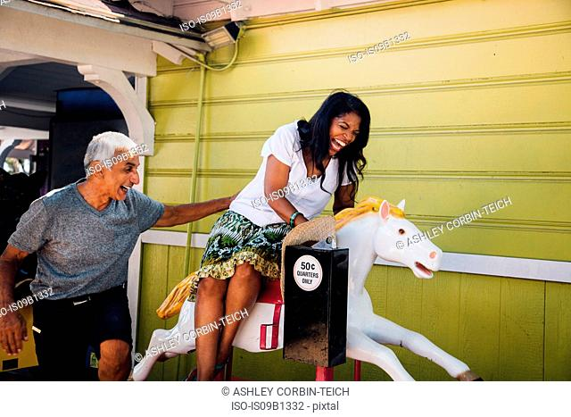 Senior woman on horse funfair ride, senior man standing beside her, laughing, Long Beach, California, USA