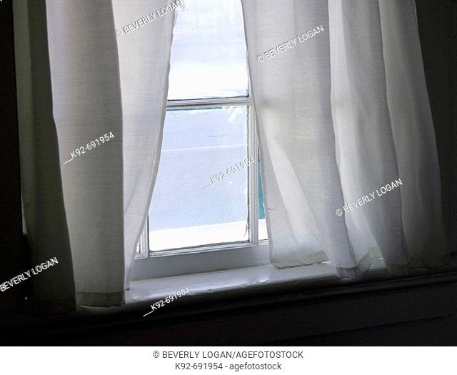 White sheer curtains on a paned window. Photo was taken on the Eastern Shore of Maryland, USA