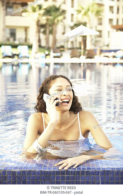 Hispanic woman talking on cell phone in pool