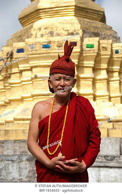 Theravada Buddhism, golden stupa, monk in red robes and cap, That Xieng Tung, Muang Sing, Luang Namtha Province, Sipsongpanna, Laos, Southeast Asia, Asia