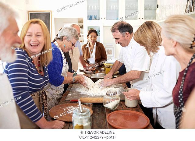 Senior friends enjoying pizza cooking class, making dough