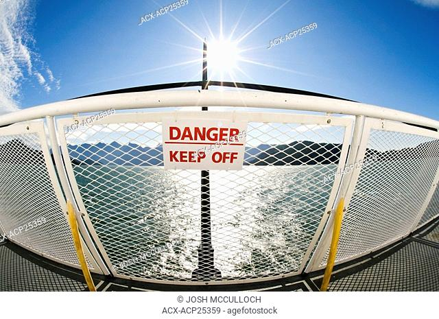 A sign on a ferry railing states 'Danger - Keep Off'