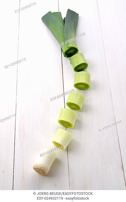 sliced organic leek on white wooden table