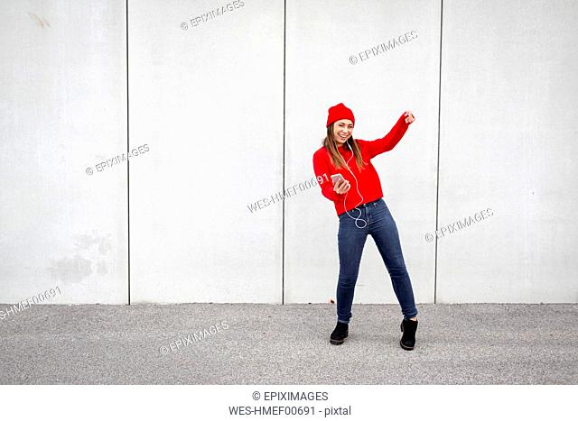 Woman wearing red pullover and wolly hat and dancing in front of a wall