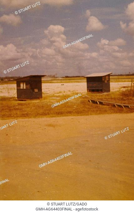 Two small, wooden structures can be seen at the air terminal, flat ground and low vegetation make up the background, Phu Bai Combat Base, Vietnam, 1964