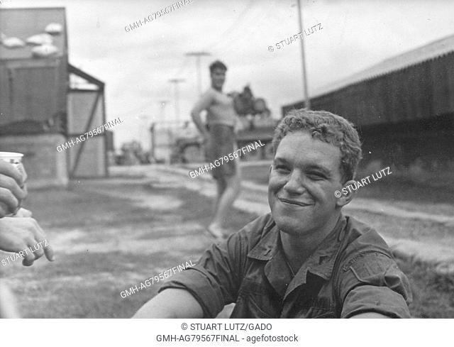 A United States Army soldier smiling while he is sitting on the ground, another soldier wearing only a towel in the background is trying to get the attention of...