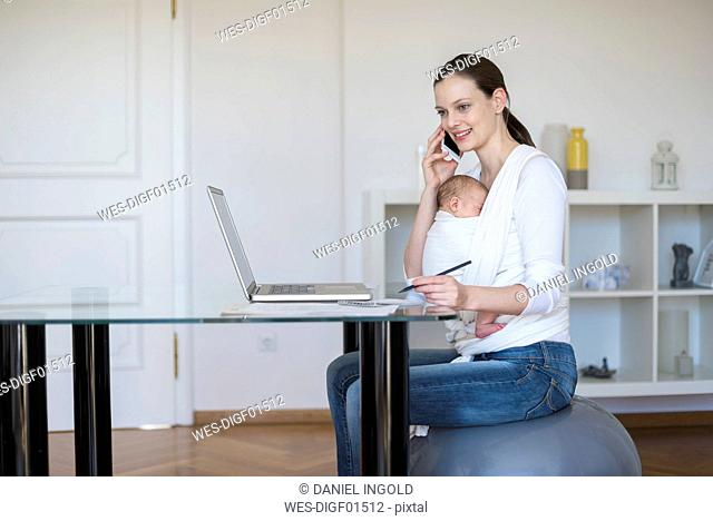 Mother with baby girl in sling working from home
