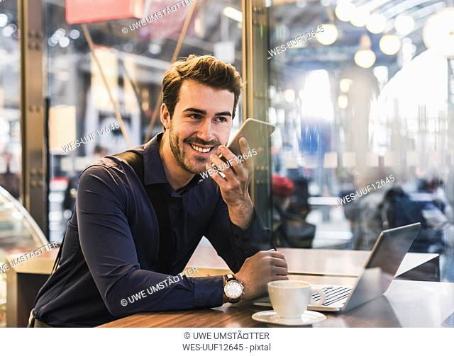 Smiling young businessman in a cafe at train station with cell phone and laptop