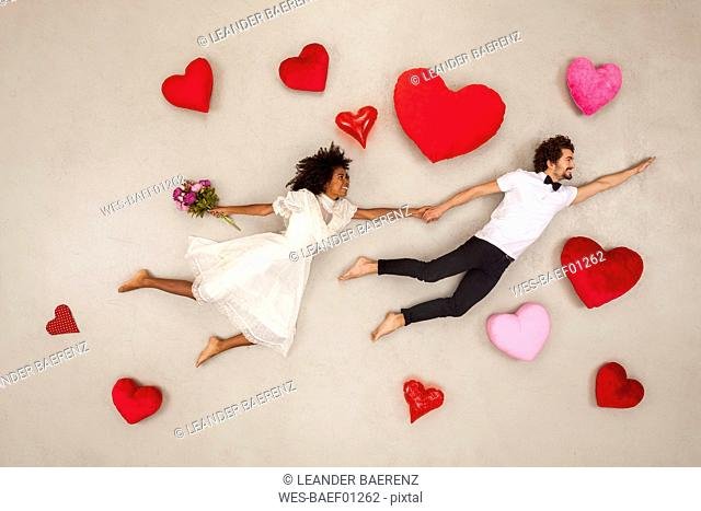 Young couple falling in love with hearts around