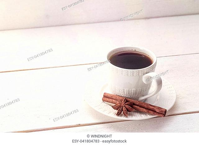 White coffee cup with cinnamon and anise on a white wooden table. Space for text