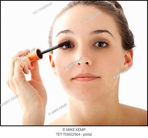 Studio portrait of young woman applying mascara