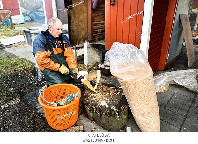 Mature fisherman cutting log by fireplace