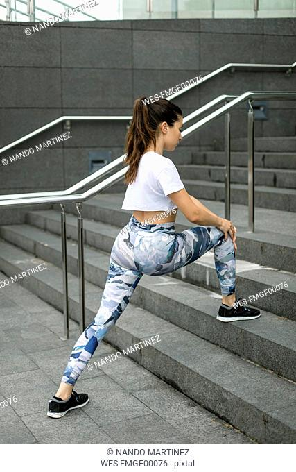 Young woman doing stretching exercise on stairs