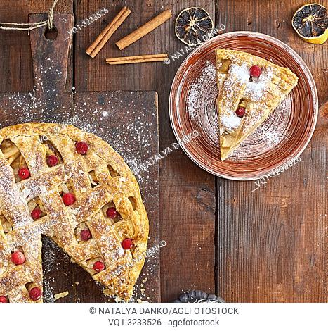 apple pie on a rectangular old brown cutting board sprinkled with powdered sugar, top view