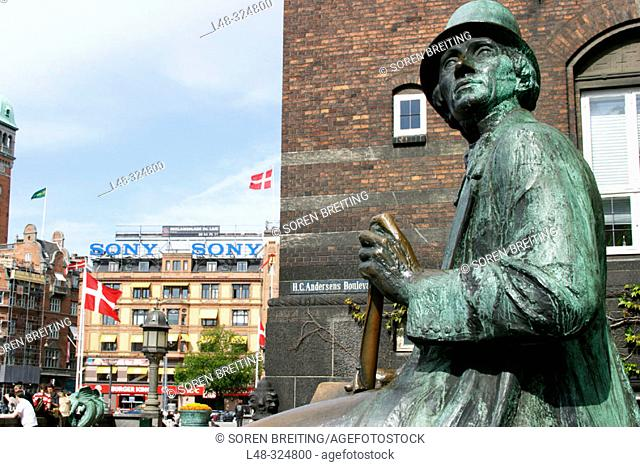 Statue of Hans Christian Andersen at H.C.Andersen's Boulevard nearTownhall Square with Danish flags at city centre of Copenhagen, Denmark