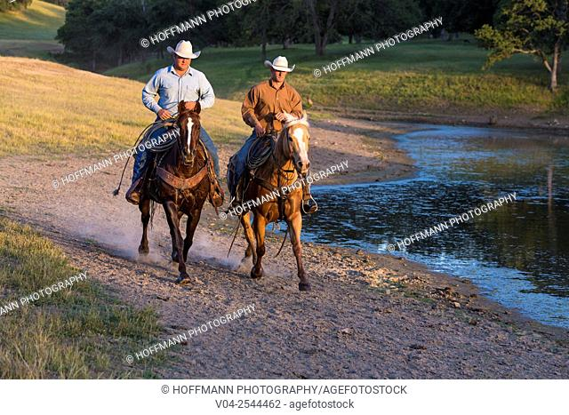Two wranglers (cowboys) on horses, riding near a pond, California, USA