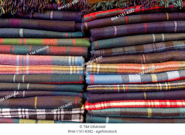 Traditional checks, plaid and Highland clan tartan lambswool throws and textiles on display for sale at Lochcarron Weavers at Lochcarron in the Highlands of...