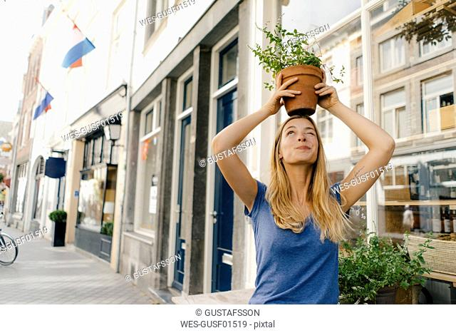 Netherlands, Maastricht, young woman balancing flowerpot on her head in the city