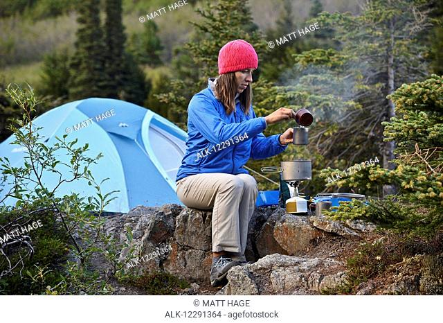 Woman backpacker prepares a meal at camp near Upper Fuller Lake in the Kenai National Wildlife Refuge on the Kenai Peninsula in South-central Alaska