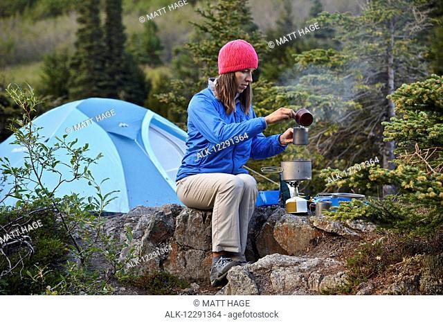 Woman backpacker prepares a meal at camp near Upper Fuller Lake in the Kenai National Wildlife Refuge on the Kenai Peninsula in South-central Alaska