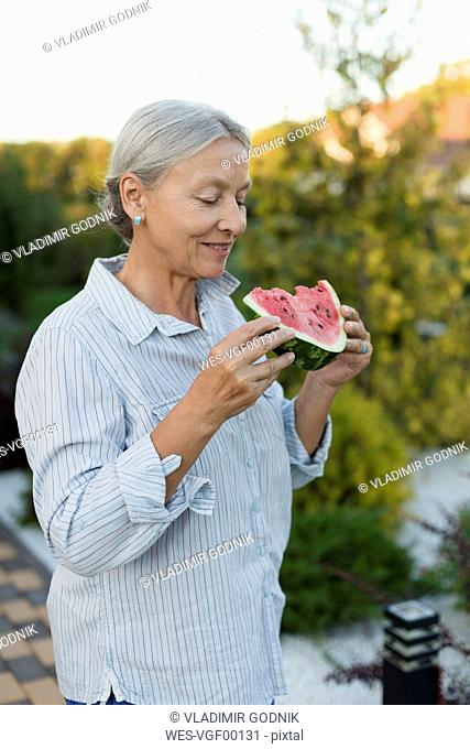 Senior woman eating watermelon slice in the garden