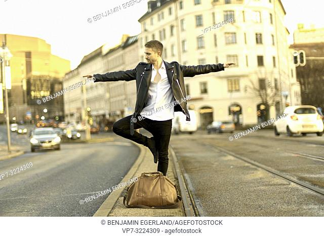 man balancing in middle of street, city, Munich, Germany