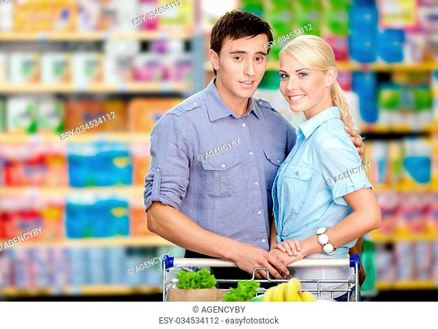 Half-length portrait of couple in the shop with cart full of food. Concept of consumerism and healthy food