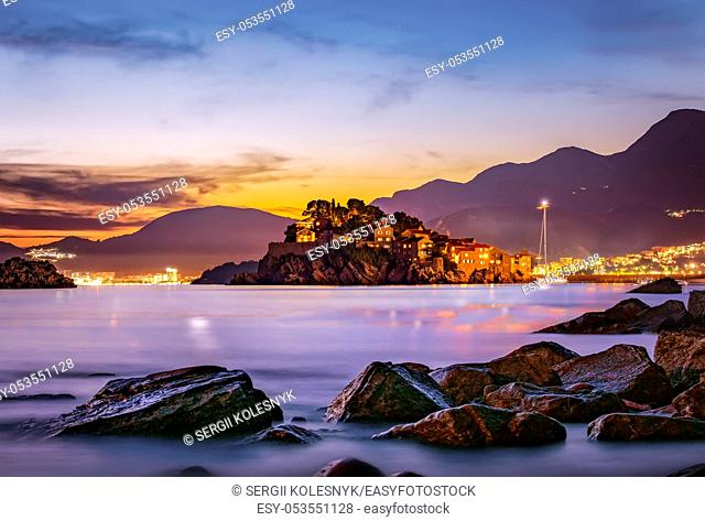 Castle Sveti Stefan on an island in the sea at sunset