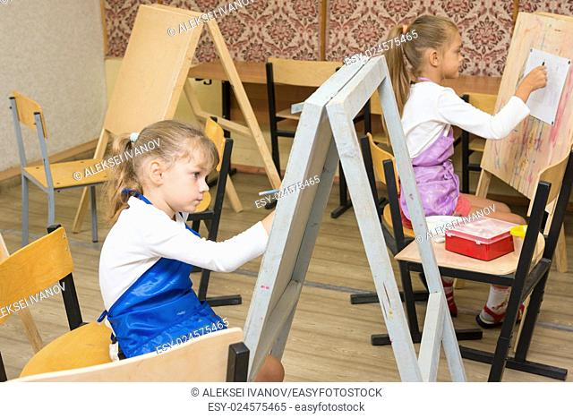 Two girls at a drawing lesson paint on easels